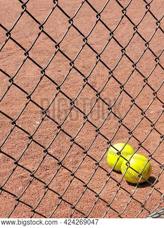 Pair Of Yellow Softballs In Dirt Behind Chain Link Fence