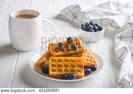 Belgian Waffles With Blueberries And Coffee On A Wood Table. Hot Morning Drink And Berries, Breakfas