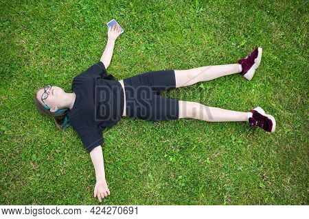 A Teenage Girl In Glasses With Multi-colored Hair Lies On The Lawn And Looks Up, A Smartphone Lies U
