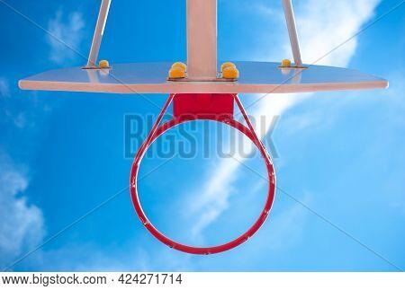 Basketball Hoop On A Background Of Blue Sky. Red Basketball Hoop. Hit The Mark. Sports, Basketball