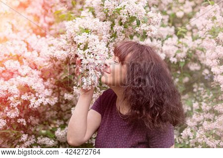 Portrait Nice Woman Of Forty Five Years Old With Brown Hair. Stands Near Large Flowering Bush And Sn