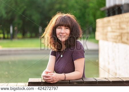Portrait Nice Woman Of Forty Five Years Old With Brown Hair, Smiling Looks At The Camera Backlit. Su