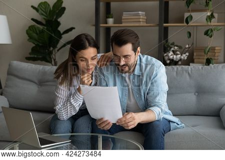 Curious Interested Young Couple Reading Paper Letter.