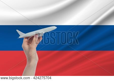 Airplane In Hand With National Flag Of Russia. Travel To Russia.