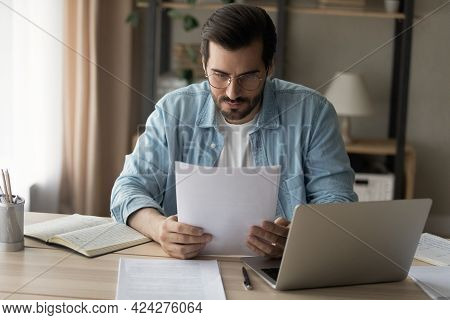 Concentrated Young Man In Glasses Looking Through Paper Correspondence.