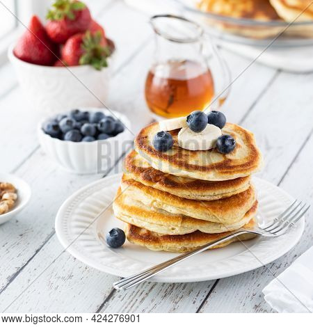 A Stack Of Buttermilk Pancakes Topped With Blueberries And Banana, Ready For Syrup To Be Poured On T