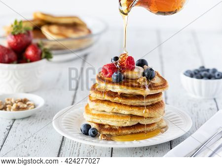 A Stack Of Buttermilk Pancakes Served With Berries And Bananas With Syrup Being Poured On Top.