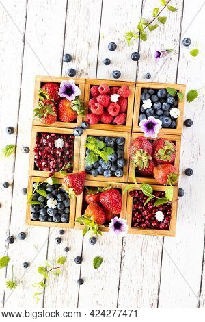 Top Down Vertical View Of An Arrangement Of Berries In Wooden Compartment Boxes With Berries And Lea