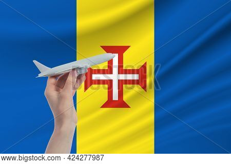 Airplane In Hand With National Flag Of Madeira. Travel To Madeira.