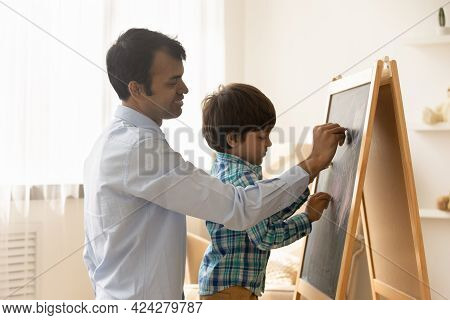 Smiling Indian Father And Small Son Paint On Whiteboard