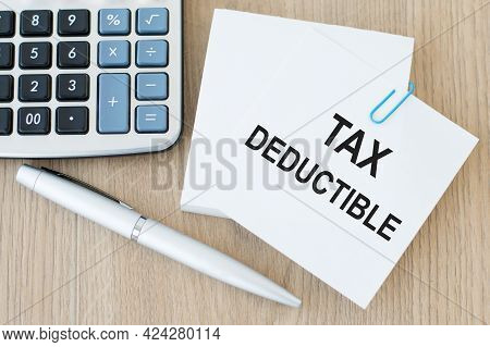 Tax Deductible Word Concept On Sticker On The Table Next To A Calculator And A Pen