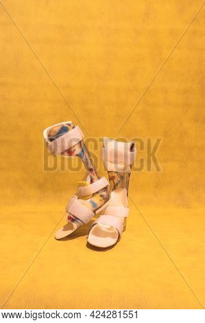 Yellow Background And An Orthopedic Device For Children's Feet For Paralysis Problems And Rehabilita