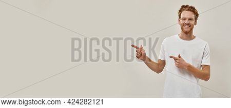 Young Redhead Man Smiles And Points With Fingers To The Left, Looks In Camera , Horizontal Shot , We
