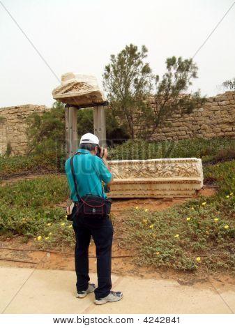 Tourist Taking Photo Of Ruined Stone, Caesarea, Israel