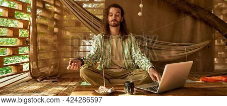 Man Tries To Meditate And Searches For The Right Music, Young Longhaired And Bearded Man Surfs The N