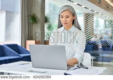 Serious Focused Asian Older Businesswoman Executive Manager Sitting At Desk Working Typing On Pc Lap