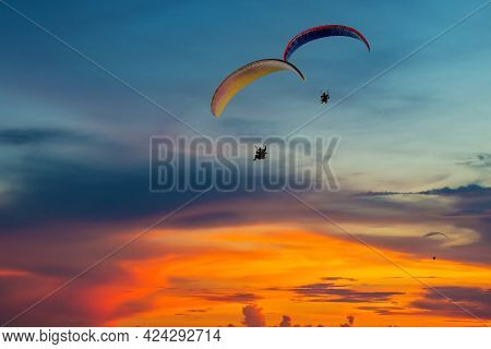 Skydiving Sunset Landscape Of Parachutist Flying In Soft Focus. Para-motor Flying Silhouette With Su
