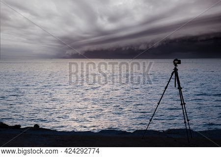 Dslr Digital Professional Camera Stand On Tripod Photographing Cloudy Storm In The Sea Before The Ra