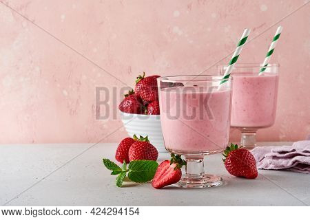 Two Strawberry Smoothie Or Milkshake With Berries And Mint In Glass On Light Pink Background. Summer
