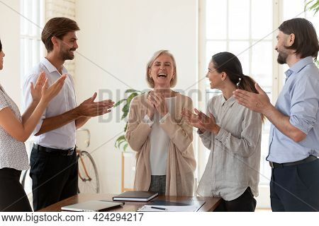 Happy Employees Applauding Middle Aged Businesswoman Executive At Meeting