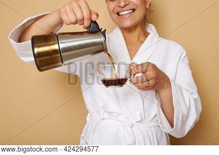 Smiling Mature Woman With Toothy Smile In White Bathrobe Pouring Coffee Drink From A Geyser Coffee M