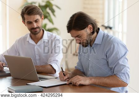 Focused Client Signing Contract After Successful Negotiations With Manager