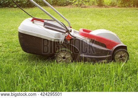 Lawn Mower On A Green Meadow. Lawn Mower In Garden. Details Of Landscaping And Gardening