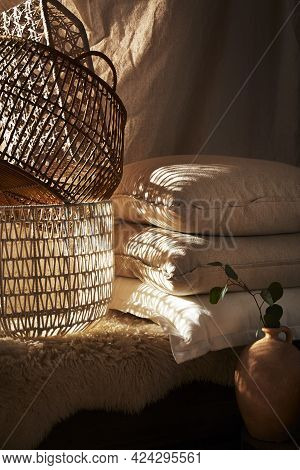 Baskets And A Stack Of Linen Pillows On A Bench Covered With A Sheepskin Texture In Moody Light. A C