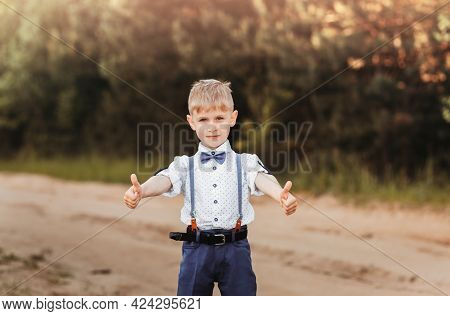 Little Boy Spreads His Hands To The Sides And Shows The Class. Children's Emotions. Shows Two-handed