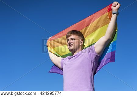 Portrait Of Young Happy Proud Gay Man, Handsome Guy Is Waving Rainbow Lgbt Color Gay Flag In Summer