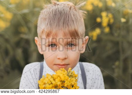 Little Boy Having Fun In Nature In The Summer. Cute Adorable Child In An Oilseed Rape Field, Close P