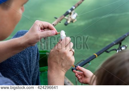 Young Adult Happy Caucasian Male Angler Person Showing Son Extracting Hool Of Fresh Catch Of Small P