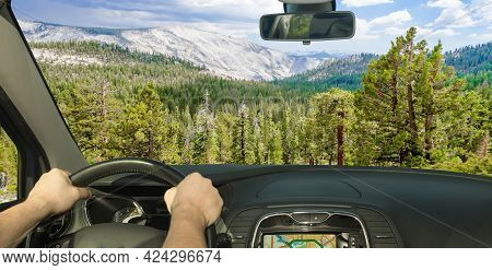 Driving A Car In Towards A Beautiful Green Valley Inside Yosemite National Park, California, Usa