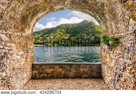 Scenic Rock Arch Balcony Overlooking A Tropical Beach In Moorea, French Polynesia