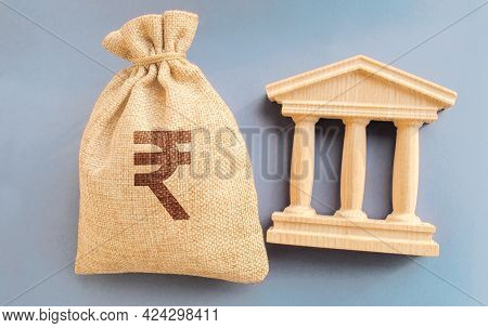 Indian Rupee Money Bag And Government Building. Business And Finance Concept. Deposit, Loan And Inve