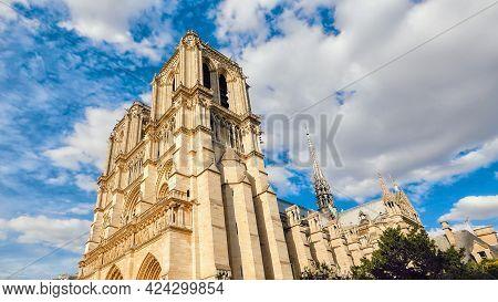 Notre Dame De Paris On Background Of Blue Cloudy Sky In Paris In Summer.