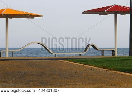 A Bench For Relaxation Stands In A City Park On The Shores Of The Mediterranean Sea On The Sesere Of