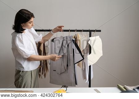 Female Fashion Designer Looking Over Paper Patterns For Sewing Hanging On Hangers In Studio Space. Y
