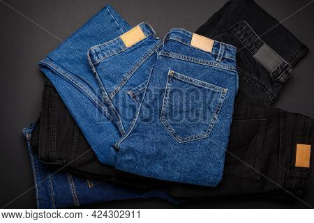 Blue Denim Jeans On Pile Of Jeans Pants. Top View Of Variety Of Denim Jean Textiles On Black Backgro
