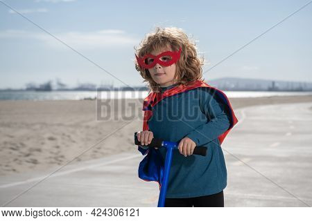 Child On Scooter In Park. Power Kids, Super Hero Child In A Superhero Raincoat. Kids Learn To Skate