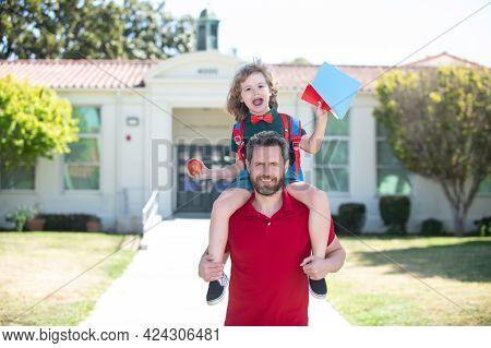 Outdoor School. Parent And Pupil Of Primary School Go Piggyback Ride.