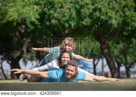 Happy Family On Summer Walk. Father Mother And Child Walking In The Park. Parents Giving Child Piggy