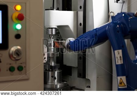 Cnc Machine And Robotic Arm Loading And Unloading Workpieces. Selective Focus.