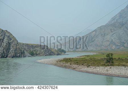 Beautiful Misty Mountain Landscape With Wide Mountain River. Dark Green Gloomy Scenery With Big Moun