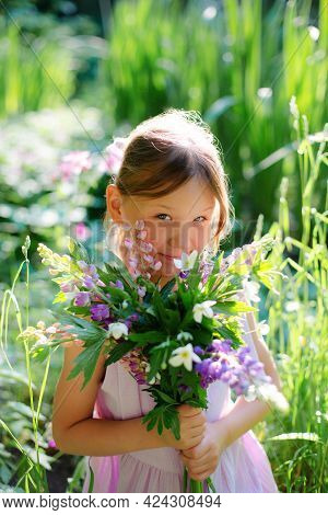 Six Year Old Girl With Bouquet Of Flowers In The Forest.