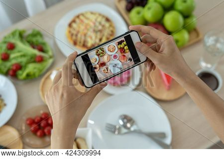 A Reviewer's Hand Using A Mobile Phone To Take Pictures Of Food At A Restaurant Table.take Photo To