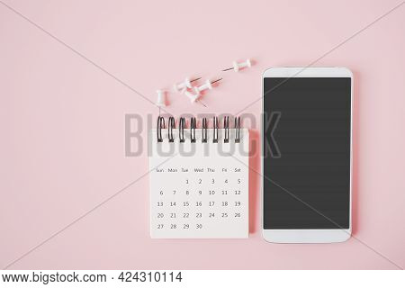 White Smart Phone With Clipping Path On Touchscreen , Opened Calendar And Thumbtacks On Sweet Pastel
