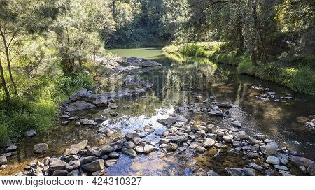 Light And Shadows On Shallow Water Flowing Over Rocks In A Creek In The Australian Bush