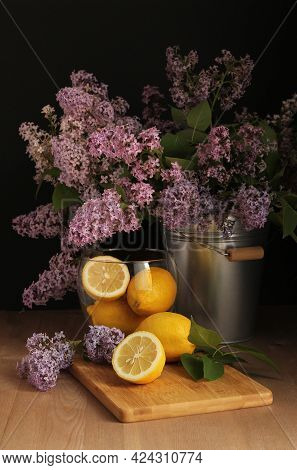 A Bouquet Of Lilacs In A Bucket. Still Life In The Flemish Style. Lemons. Spring. Still Life In A Lo