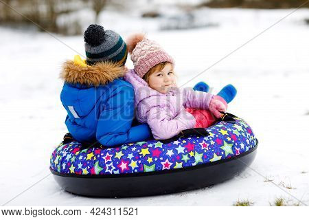 Active Toddler Girl And School Boy Sliding Together Down The Hill On Snow Tube. Happy Children, Sibl